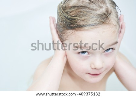 Child in the bathtub. Girl washes in the bathroom - stock photo