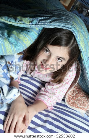 child in the bed with alarm clock