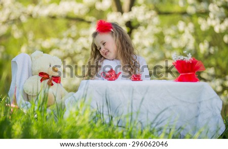child in the garden drinking tea - stock photo