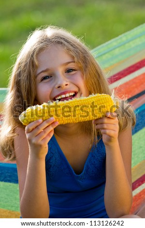 Child in the garden - lovely girl eating corn on the cob (GMO free) - stock photo