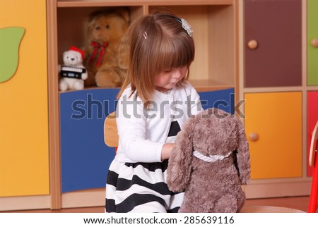 Child in the nursery playing with teddy bear