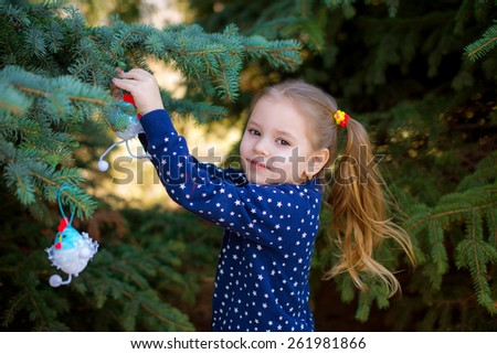 child in the spring park decorated Christmas tree decorations Easter - stock photo