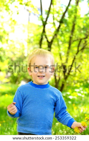 child in the spring park on a background of green grass and foliage - stock photo