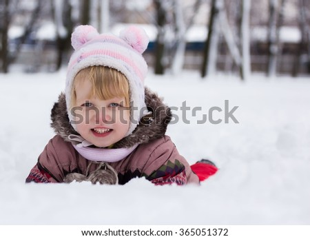 Child in winter. Happy girl on snow