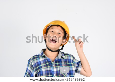 Child in work clothes and pointing isolated on gray background. - stock photo