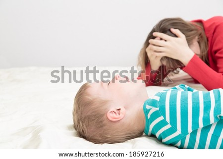 child is crying while mother is tired, difficult parenting - stock photo