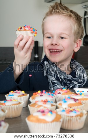 Child is decorating the just baked cupcakes