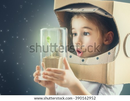 Child is dressed in an astronaut costume. Child sees a sprout in a glass case. The concept of environmental protection. - stock photo