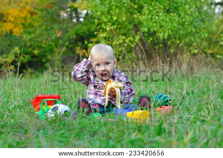 child is eating a banana in wood - stock photo