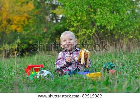 child is eating a banana. soiled. Laughs - stock photo