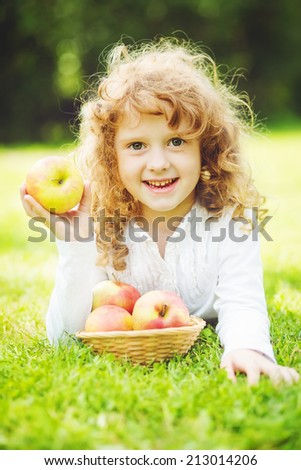 Child is eating red apple. - stock photo