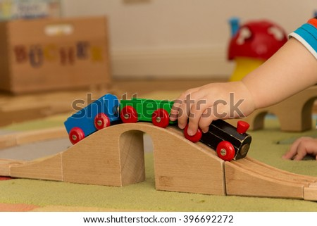 child is playing with wooden railroad - stock photo