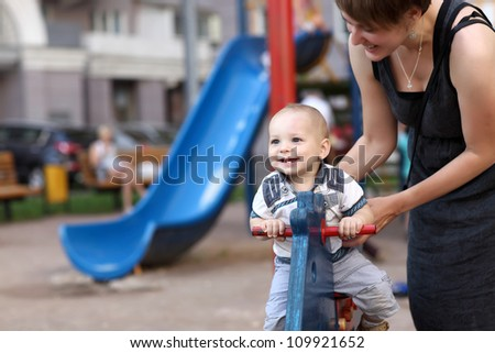 Child is swinging on spring toy horse at playground - stock photo