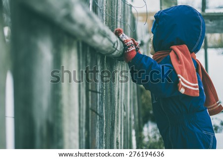 child is watching over the fence - stock photo