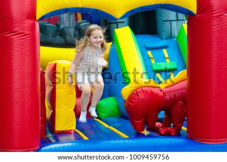 Child jumping on colorful playground trampoline. Kids jump in inflatable bounce castle on kindergarten birthday party Activity and play center for young child. Little girl playing outdoors in summer.