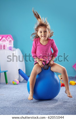 Child jumping on gymnastic ball