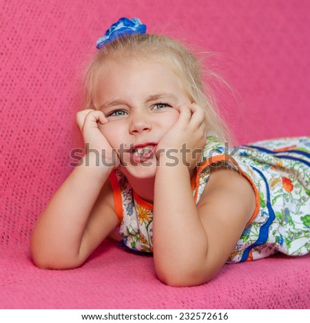 Child.  Kid. Adorable little girl lying on pink  background. Capricious, sad. - stock photo