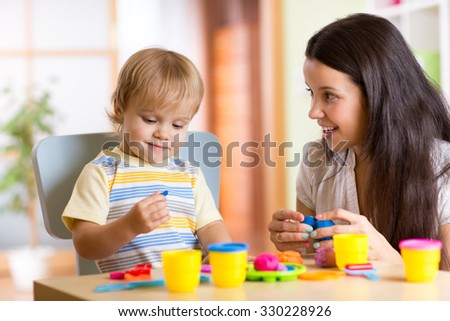 child kid boy and mother play colorful clay toy at nursery or kindergarten - stock photo