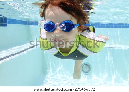 Child, kid, diving and swimming in pool underwater, summer or sports theme