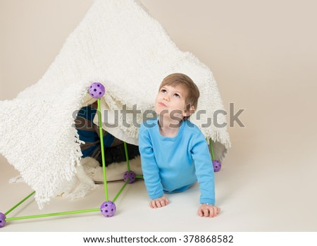 Child, kid, playing with a tent or fort made out of blankets