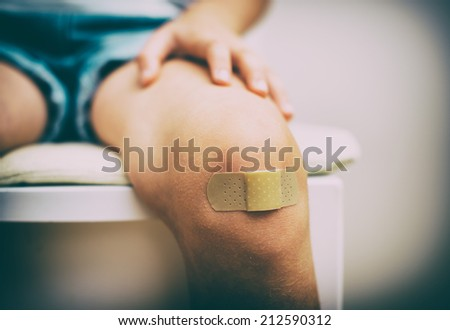 Child knee with an adhesive bandage. Vintage effect. - stock photo