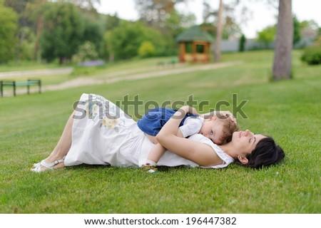 child laying on relaxing mother in meadow