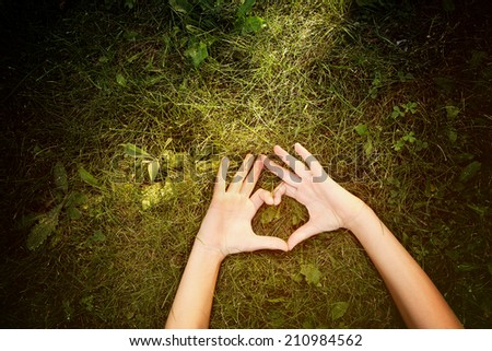 Child laying outdoors  making a heart shape. Instagram effect - stock photo