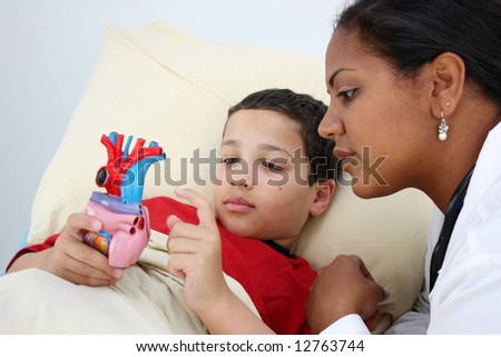 Child laying sick in bed at the hospital with doctor - stock photo