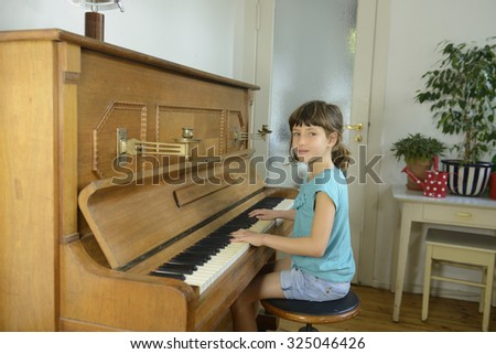 Child learning to play piano at home - stock photo