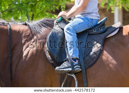 Child leg is the correct position on the saddle for riding a horse - stock photo