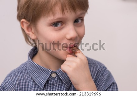 Child licks chocolate glaze with finger. closeup of boy holding jar and eating chocolate - stock photo