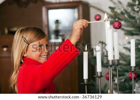 Child lighting Christmas candles in front of a Christmas tree - stock photo