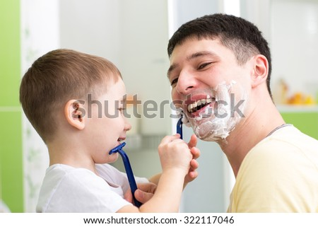 Child little boy shaving his father in bathroom  - stock photo