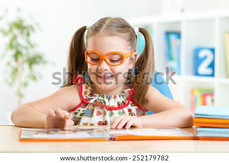 Child little girl reading a book at home or primary school - stock photo