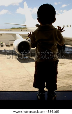 child looking at a plane