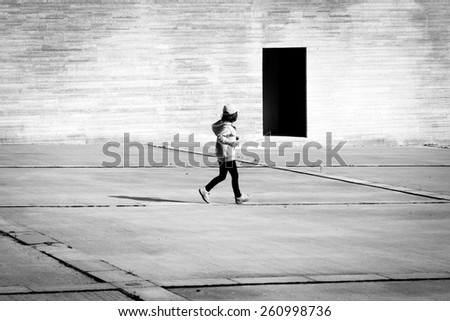 Child looking  at dark black and white door - stock photo