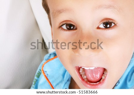 Child looking at the camera playing and shouting. Face close up