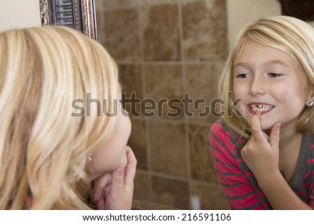 Child looking in mirror and pointing at missing front tooth