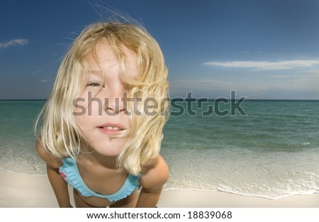 Child looking into the camera on a beautiful sunny day at the beach