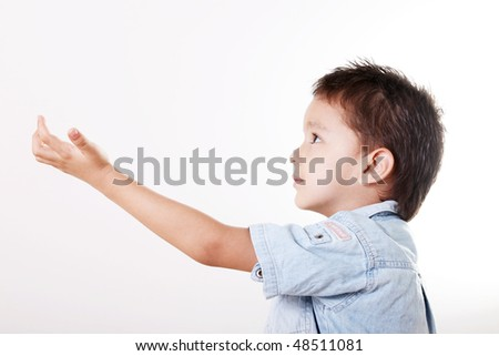 Child looking up with hand extended - stock photo