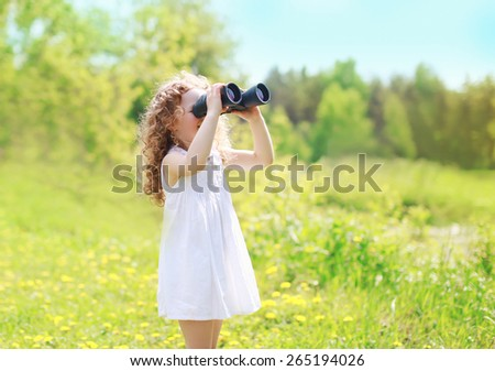 Child looks in binoculars outdoors in sunny summer day - stock photo