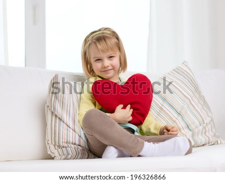 child, love and happiness concept - smiling little girl with red heart at home - stock photo