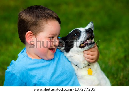 Child lovingly embraces his pet dog - stock photo