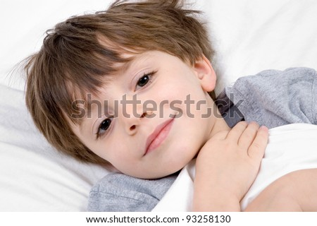 Child lying in bed with blanket