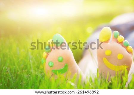 Child lying on green grass. Kid having fun outdoors in spring park - stock photo