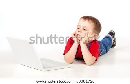 Child lying on the floor with laptop on white background - stock photo