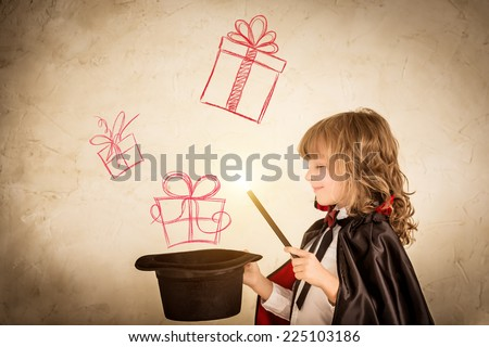 Child magician holding a top hat with drawn gift boxes. Christmas holiday concept - stock photo