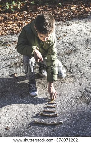 Child make pine tree of wooden sticks - stock photo