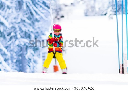 Child on a button ski lift going uphill in the mountains on a sunny snowy day. Kids in winter sport school in alpine resort. Family fun in the snow. Little skier learning and exercising on a slope. - stock photo