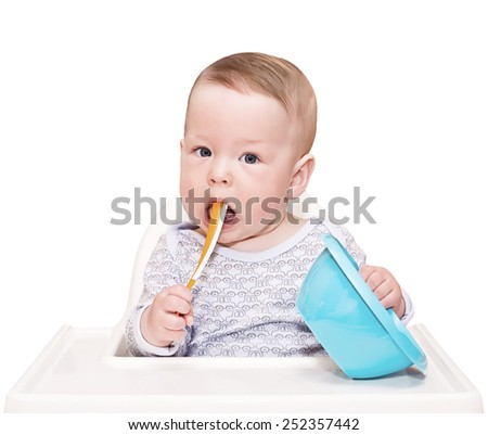 child on chair for feeding with a plastic spoon and a plate, isolated on white - stock photo